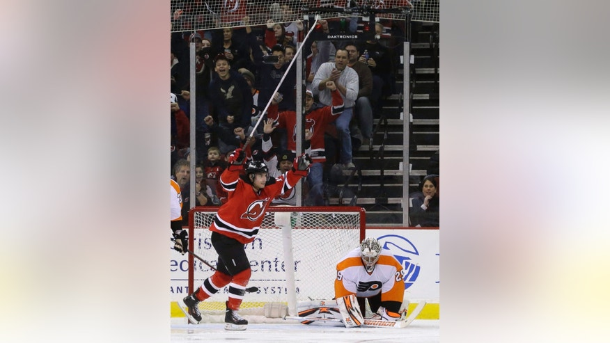 New Jersey Devils' Adam Henrique, left, celebrates after scoring a goal on Philadelphia Flyers goalie Ray Emery during the first period of an NHL hockey game, Tuesday, Jan. 7, 2014, in Newark, N.J. (AP Photo/Julio Cortez)