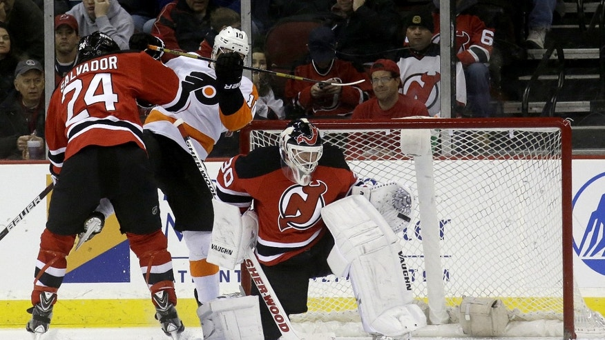 New Jersey Devils goalie Martin Brodeur, right, deflects a shot by the Philadelphia Flyers as defenseman Bryce Salvador (24) defends Philadelphia Flyers center Brayden Schenn during the second period of an NHL hockey game, Tuesday, Jan. 7, 2014, in Newark, N.J. (AP Photo/Julio Cortez)