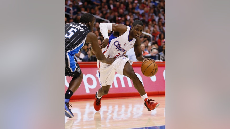 Los Angeles Clippers' Darren Collison, right, drives around Orlando Magic's Victor Oladipo, left, during the first half of an NBA basketball game in Los Angeles, Monday, Jan. 6, 2014. (AP Photo/Danny Moloshok)