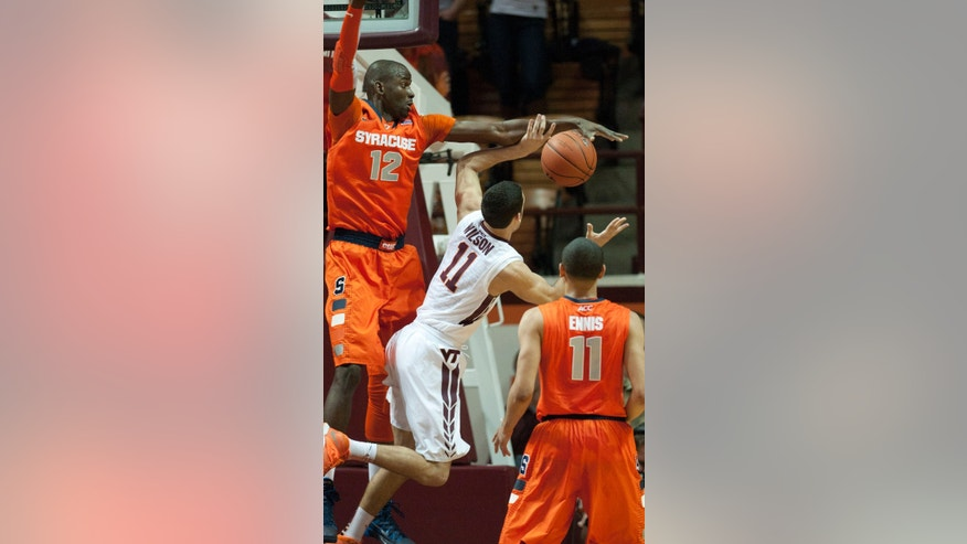 Syracuse's Baye Moussa Keita (12) blocks the shot of Virginia Tech's Devin Wilson during the first half of an NCAA college basketball game Tuesday, Jan. 7, 2014, in Blacksburg, Va. (AP Photo/Don Petersen)