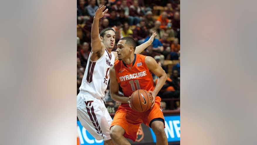 Syracuse's Tyler Ennis (11) looks to pass against Virginia Tech's Devin Wilson during the first half of an NCAA college basketball game Tuesday, Jan. 7, 2014, in Blacksburg, Va. (AP Photo/Don Petersen)