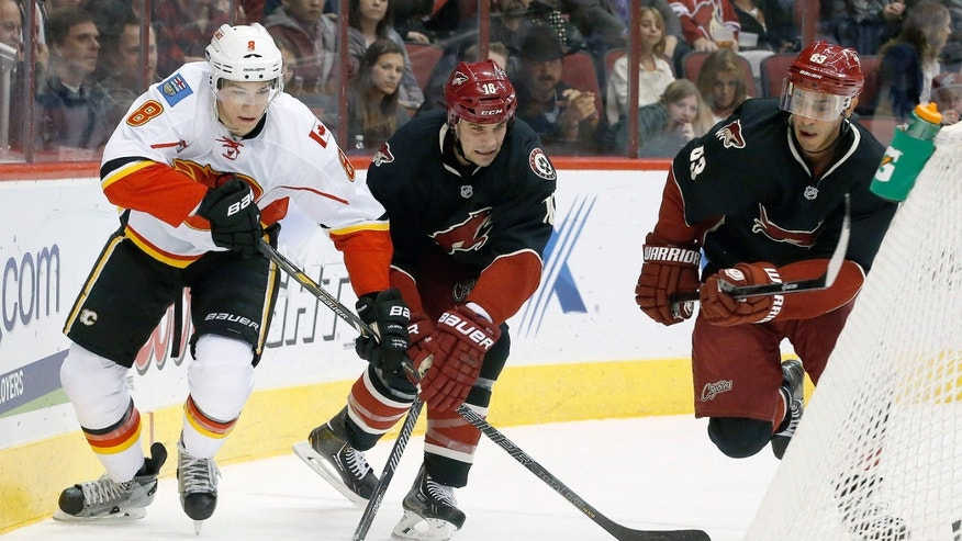Calgary Flames' Joe Colborne (8) battles Phoenix Coyotes' Rostislav Klesla (16), of the Czech Republic, and Mike Ribeiro (63) for the puck during the first period of an NHL hockey game, Tuesday, Jan. 7, 2014, in Glendale, Ariz. (AP Photo/Ross D. Franklin)