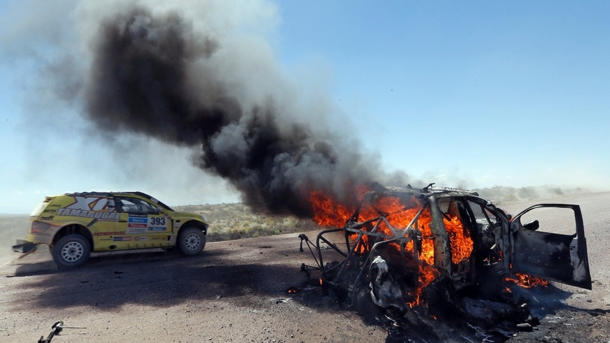 The car of Javier Campillay of Chile and co-pilot Jose Ocampo of Argentina, left, drives by what remains of the Toyota of driver Bauyrzhan Issabayev and co-pilot Gabdulla Ashimov, both of Kazakhstan, during the second stage of the Dakar Rally between the cities of San Luis and San Rafael in San Rafael, Argentina,  Monday, Jan. 6, 2014. (AP Photo/Jean-Paul Pleissier, Pool)