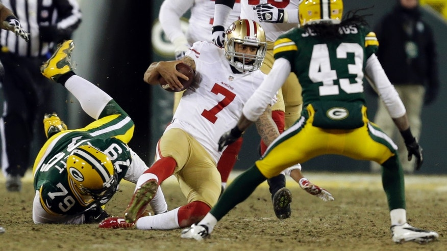 San Francisco 49ers quarterback Colin Kaepernick (7) slides as he runs against Green Bay Packers defense during the second half of an NFL wild-card playoff football game, Sunday, Jan. 5, 2014, in Green Bay, Wis. (AP Photo/Mike Roemer)