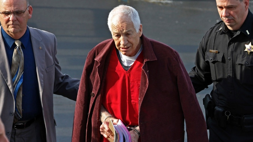 FILE - In this Jan. 10, 2013 file photo, former Penn State University assistant football coach Jerry Sandusky, center, leaves the Centre County Courthouse after attending a post-sentence motion hearing in Bellefonte, Pa. Sandusky is expected to participate in the proceeding to have his Penn State pension restored by video conference. The proceeding begins on Tuesday, Jan. 7, 2014. Sandusky lost a $4,900-a-month pension in October 2012, when he was sentenced to 30 to 60 years in prison for child sexual abuse. (AP Photo/Gene J. Puskar, File)
