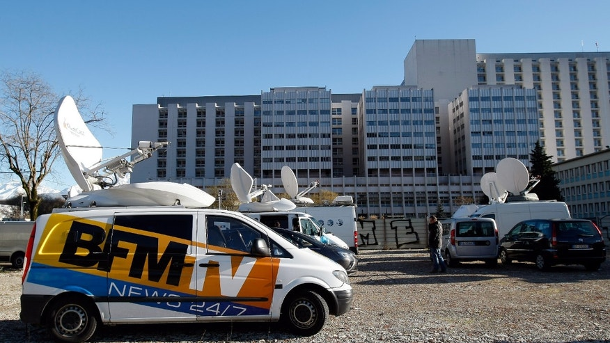 A TV van is parked in front of the Grenoble hospital, French Alps, Sunday, Jan. 5 , 2014, where former seven-time Formula One champion Michael Schumacher is being treated after sustaining a head injury during a ski accident. Schumacher has been in a medically induced coma since Sunday, Dec. 29, 2013, when he struck his head on a rock while on a family vacation. (AP Photo/Claude Paris)