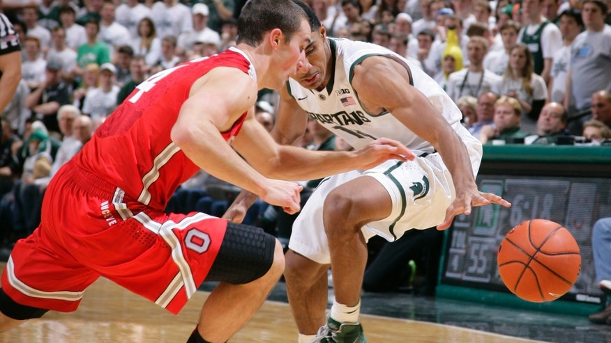 Michigan State's Gary Harris, right, and Ohio State's Aaron Craft chase a loose ball during the second half of an NCAA college basketball game, Tuesday, Jan. 7, 2014, in East Lansing, Mich. Michigan State won 72-68 in overtime. (AP Photo/Al Goldis)