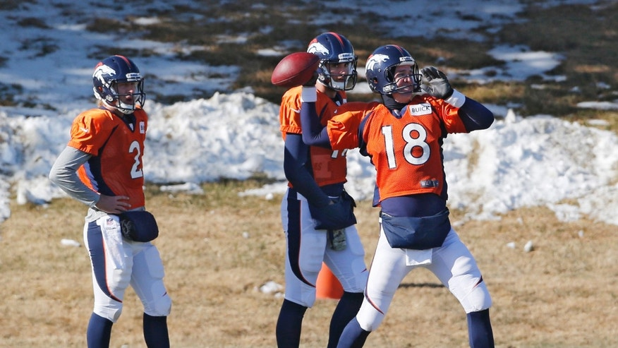 Denver Broncos quarterback Peyton Manning (18) throws a pass at practice for the football team's NFL playoff game against the San Diego Chargers at the Broncos training facility in Englewood, Colo., on Wednesday, Jan. 8, 2014. Backup quarterbacks Zac Dysert (2) and Brock Osweiler (17) watch. (AP Photo/Ed Andrieski)