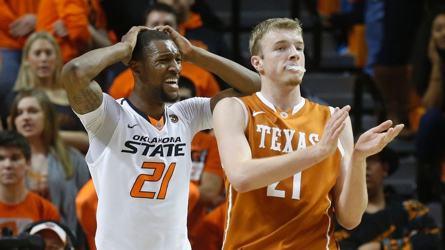 Oklahoma State post Kamari Murphy (21) holds his head and Texas forward Connor Lammert (21) applauds after Murphy was called for a foul during the first half of an NCAA college basketball game in Stillwater, Okla., Wednesday, Jan. 8, 2014. (AP Photo/Sue Ogrocki)