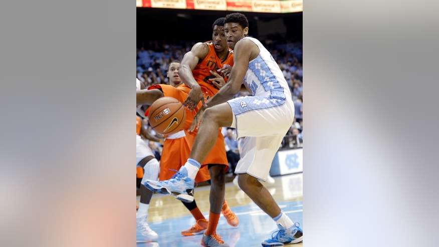 North Carolina's Isaiah Hicks, right, and Miami's Garrius Adams struggle for possession of the ball during the first half of an NCAA college basketball game in Chapel Hill, N.C., Wednesday, Jan. 8, 2014. (AP Photo/Gerry Broome)