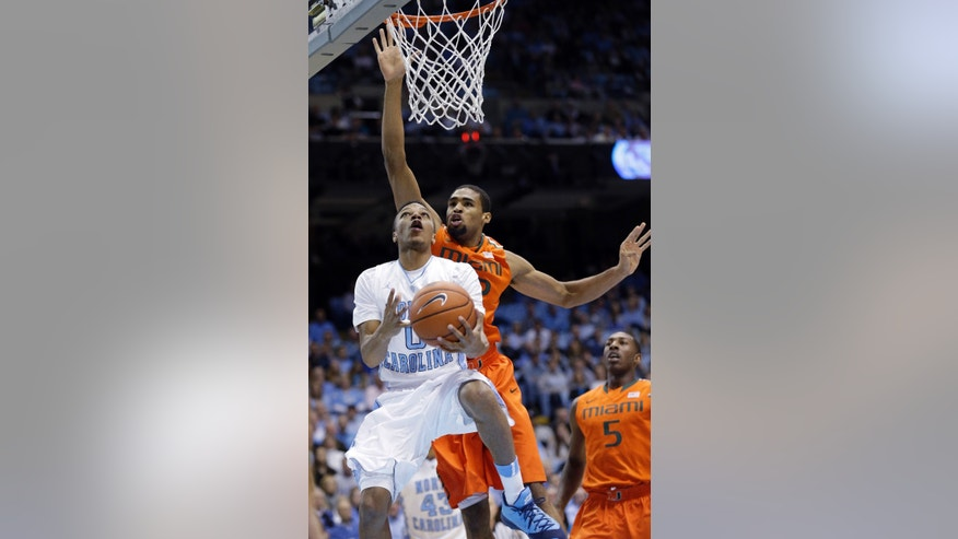North Carolina's Nate Britt (0) drives to the basket as Miami's Donnavan Kirk defends during the first half of an NCAA college basketball game in Chapel Hill, N.C., Wednesday, Jan. 8, 2014. (AP Photo/Gerry Broome)