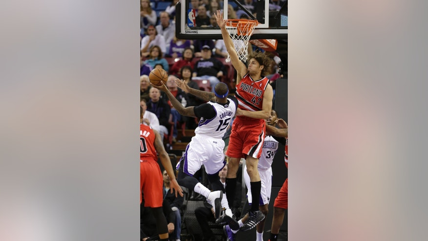 Portland Trail Blazers center Robin Lopez, right, tries to block the shot of Sacramento Kings center DeMarcus Cousins, left, during the first quarter of an NBA basketball game in Sacramento, Calif., Tuesday, Jan. 7, 2014. (AP Photo/Rich Pedroncelli)