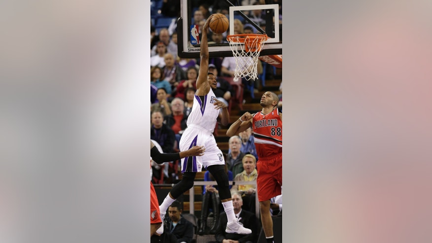 Sacramento Kings forward Rudy Gay, left, goes up for the stuff against Portland Trail Blazers forward Nicolas Batum, right, of France, during the first quarter of an NBA basketball game in Sacramento, Calif., Tuesday, Jan. 7, 2014. (AP Photo/Rich Pedroncelli)
