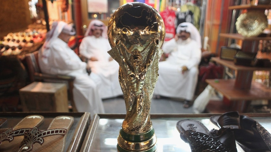 DOHA, QATAR - OCTOBER 24:  Arab men sit at a shoemaker's stall with a replica of the FIFA World Cup trophy in the Souq Waqif traditional market on October 24, 2011 in Doha, Qatar. Qatar will host the 2022 FIFA World Cup football competition and is slated to tackle a variety of infrastructure projects, including the construction of new stadiums.  (Photo by Sean Gallup/Getty Images)