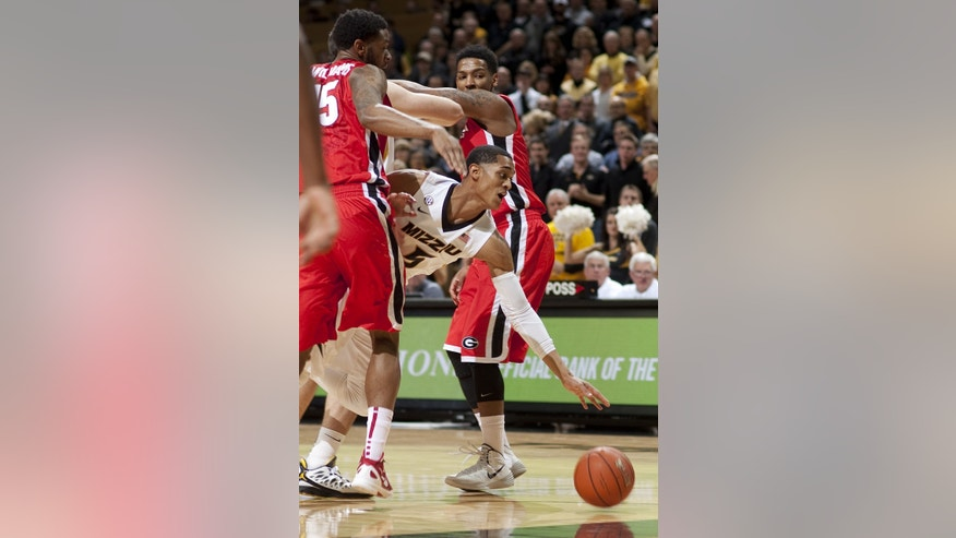 Missouri's Jordan Clarkson, center, fights his way between Georgia's Charles Mann, right, and Georgia's Donte' Williams, left, as he moves toward the basket during the first half of an NCAA college basketball game Wednesday, Jan. 8, 2014, in Columbia, Mo. (AP Photo/L.G. Patterson)