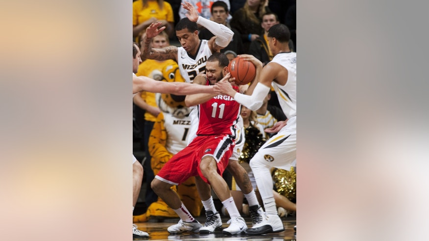 Georgia's Cameron Forte, center, tries to get a handle on a rebound between Missouri's Jordan Clarkson, right, and Jabari Brown, left, during the first half of an NCAA college basketball game Wednesday, Jan. 8, 2014, in Columbia, Mo. (AP Photo/L.G. Patterson)