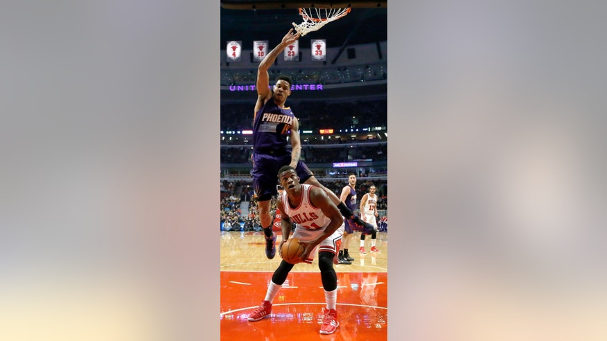 Chicago Bulls guard Jimmy Butler, right, waits for Phoenix Suns guard Gerald Green (14) to clear the area before scoring during the first half of an NBA basketball game, Tuesday, Jan. 7, 2014, in Chicago. (AP Photo/Charles Rex Arbogast)