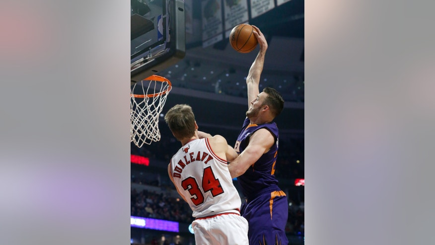 Phoenix Suns center Miles Plumlee, right, dunks over Chicago Bulls forward Mike Dunleavy during the first half of an NBA basketball game, Tuesday, Jan. 7, 2014, in Chicago. (AP Photo/Charles Rex Arbogast)