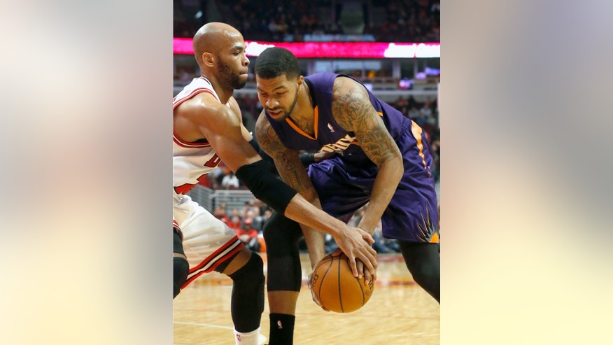 Chicago Bulls forward Taj Gibson, left, pressures Phoenix Suns power Markieff Morris during the first half of an NBA basketball game, Tuesday, Jan. 7, 2014, in Chicago. (AP Photo/Charles Rex Arbogast)