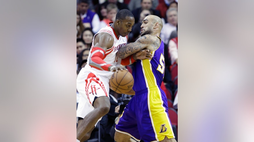 Houston Rockets' Dwight Howard, left, is fouled by Los Angeles Lakers' Robert Sacre in the first half of an NBA basketball game on Wednesday, Jan. 8, 2014, in Houston. (AP Photo/Pat Sullivan)