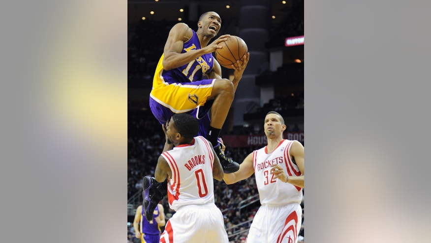 Los Angeles Lakers' Wesley Johnson (11) leaps over Houston Rockets' Aaron Brooks (0) to score two points as Rockets' Francisco Garcia (32) looks on in the first half of an NBA basketball game on Wednesday, Jan. 8, 2014, in Houston. (AP Photo/Pat Sullivan)