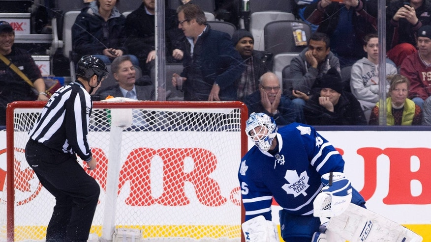 Toronto Maple Leafs goalie Jonathan Bernier reacts after mishandling the puck and allowing a New York Islanders goal during second period of an NHL hockey game in Toronto, Tuesday, Jan. 7, 2014. (AP Photo/The Canadian Press, Nathan Denette)