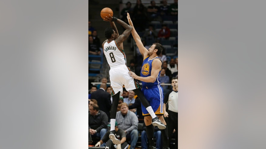 Milwaukee Bucks' Larry Sanders (8) shoots over Golden State Warriors' Andrew Bogut during the first half of an NBA basketball game Tuesday, Jan. 7, 2014, in Milwaukee. (AP Photo/Jeffrey Phelps)