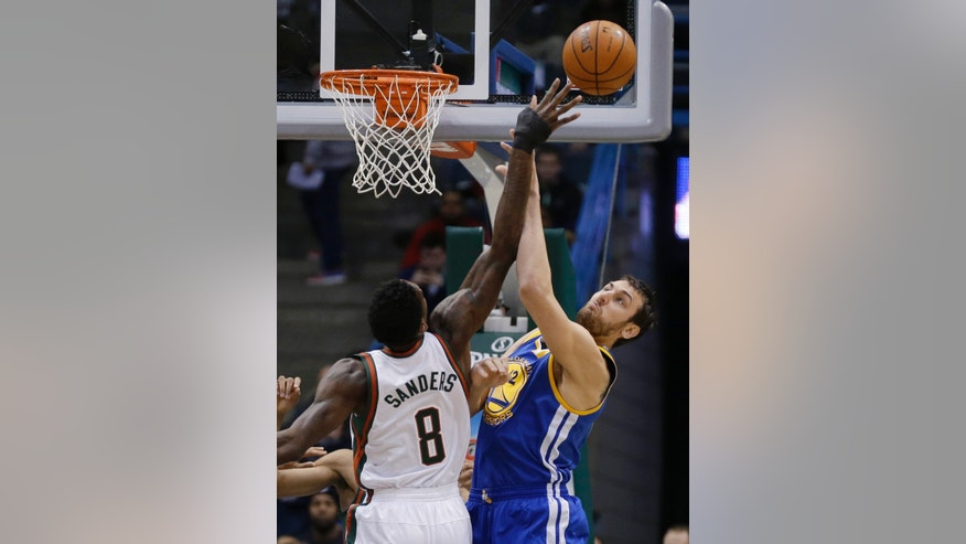 Milwaukee Bucks' Larry Sanders (8) and Golden State Warriors' Andrew Bogut, right, reach for a rebound during the first half of an NBA basketball game Tuesday, Jan. 7, 2014, in Milwaukee. (AP Photo/Jeffrey Phelps)