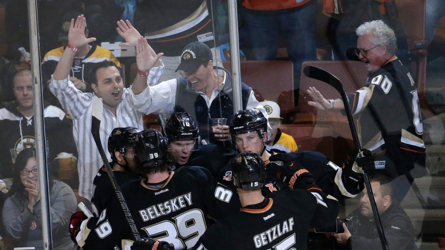 Fans and members of the Anaheim Ducks celebrate Corey Perry's goal against the Boston Bruins during the second period of an NHL hockey game in Anaheim, Calif., Tuesday, Jan. 7, 2014. (AP Photo/Chris Carlson)