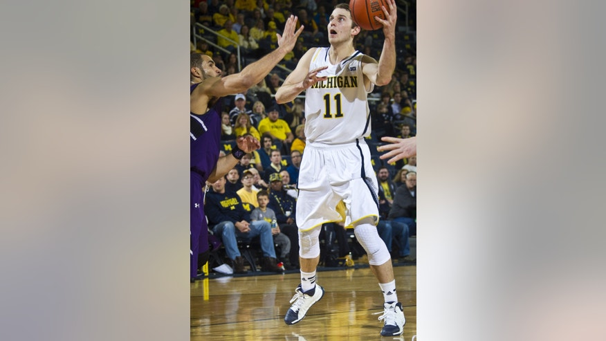 Northwestern guard Drew Crawford, left, defends against Michigan guard Nik Stauskas (11) in the first half of an NCAA college basketball game at Crisler Center in Ann Arbor, Mich., Sunday, Jan. 5, 2014. (AP Photo/Tony Ding)