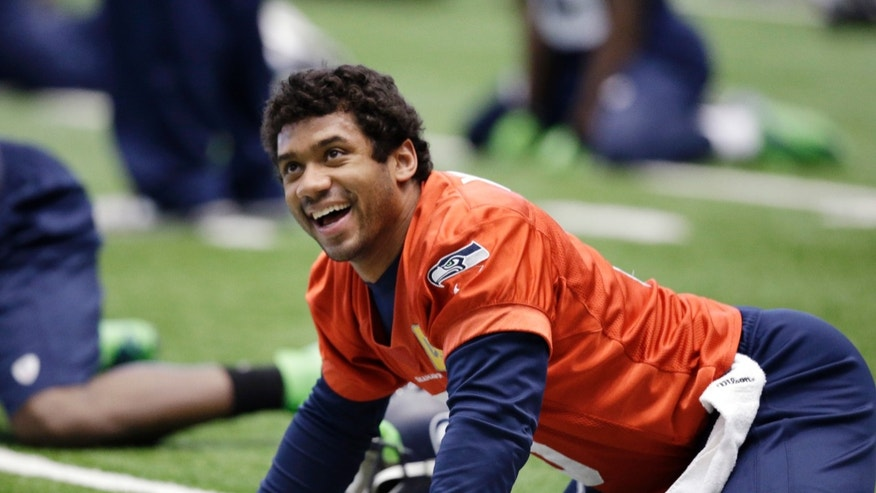 Seattle Seahawks quarterback Russell Wilson smiles as he stretches at an NFL football practice Tuesday, Jan. 7, 2014, in Kirkland, Wash. The Seahawks play the New Orleans Saints Saturday in an NFC divisional playoff game. (AP Photo/Elaine Thompson)