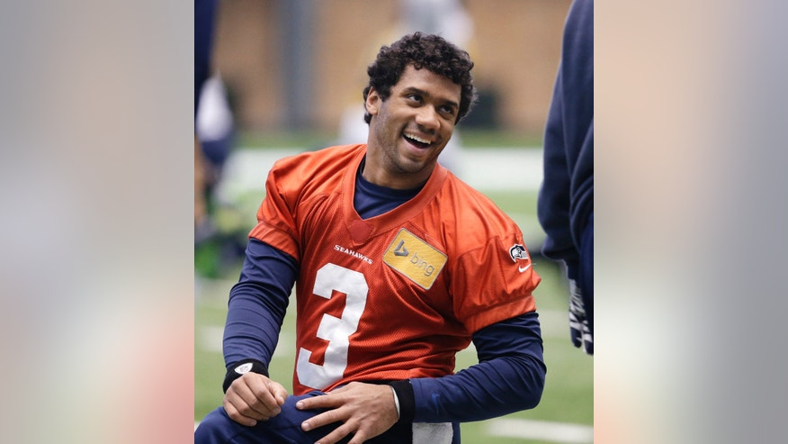 Seattle Seahawks quarterback Russell Wilson smiles as he stretches for NFL football practice Tuesday, Jan. 7, 2014, in Kirkland, Wash. The Seahawks play the New Orleans Saints Saturday in an NFC divisional playoff game. (AP Photo/Elaine Thompson)