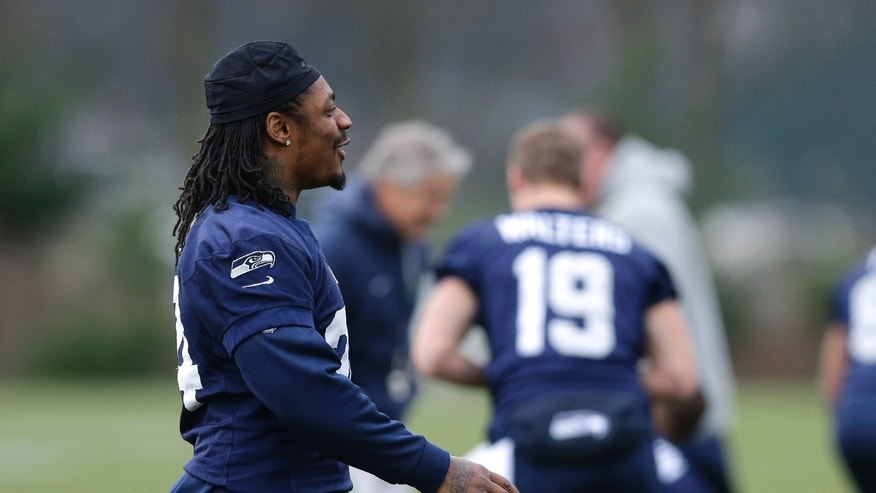 Seattle Seahawks NFL football running back Marshawn Lynch, left, walks during stretching warmups on Thursday, Jan. 2, 2014, before practice in Renton, Wash. (AP Photo/Ted S. Warren)