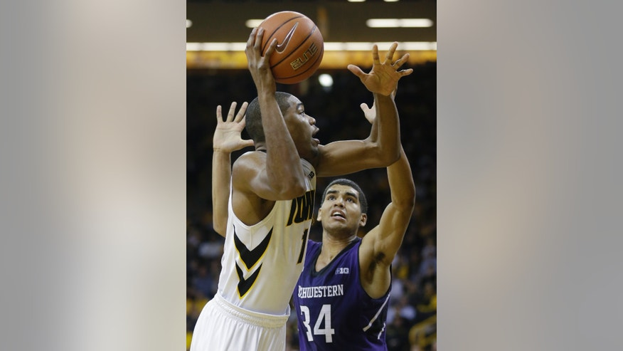 Iowa forward Melsahn Basabe, left, shoots over Northwestern forward Sanjay Lumpkin during the first half of an NCAA college basketball game, Thursday, Jan. 9, 2014, in Iowa City, Iowa. (AP Photo/Charlie Neibergall)