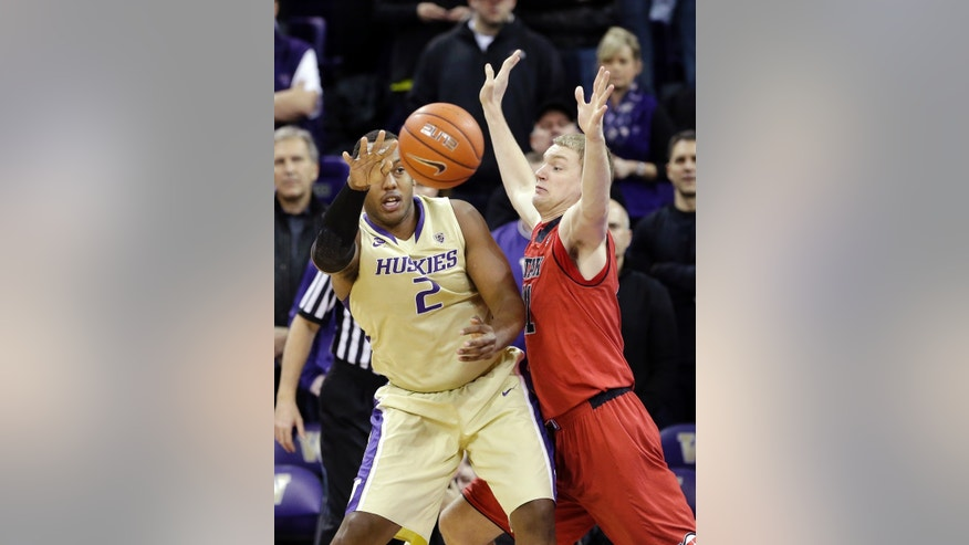Washington's Perris Blackwell (2) passes as Utah's Jeremy Olsen defends in the first half of an NCAA men's basketball game Wednesday, Jan. 8, 2014, in Seattle. (AP Photo/Elaine Thompson)