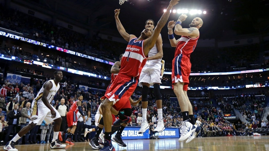 Washington Wizards small forward Trevor Ariza (1) battles for a rebound in front of center Marcin Gortat, right, and New Orleans Pelicans center Alexis Ajinca, behind, in the first half of an NBA basketball game in New Orleans, Wednesday, Jan. 8, 2014. (AP Photo/Gerald Herbert)