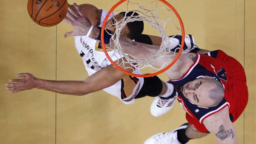 New Orleans Pelicans shooting guard Eric Gordon (10) is fouled by Washington Wizards center Marcin Gortat (4) as he goes to the basket in the first half of an NBA basketball game in New Orleans, Wednesday, Jan. 8, 2014. (AP Photo/Gerald Herbert)