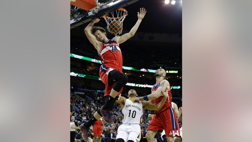 Washington Wizards power forward Jan Vesely (24) slam dunks over center Marcin Gortat, right, and New Orleans Pelicans shooting guard Eric Gordon (10) in the first half of an NBA basketball game in New Orleans, Wednesday, Jan. 8, 2014. (AP Photo/Gerald Herbert)