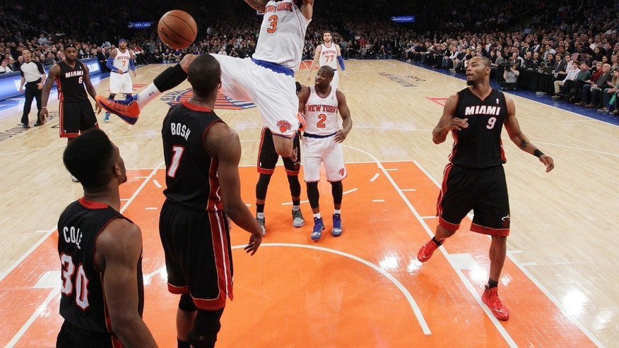 New York Knicks' Kenyon Martin (3) holds onto the rim after dunking the ball in front of Miami Heat's Chris Bosh (1) and Norris Cole (30) during the first half of an NBA basketball game on Thursday, Jan. 9, 2014, in New York. (AP Photo/Frank Franklin II)