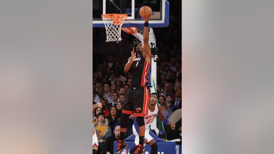Miami Heat's Chris Bosh (1) scores in front of New York Knicks' Iman Shumpert (21) during the first half of an NBA basketball game on Thursday, Jan. 9, 2014, in New York. (AP Photo/Frank Franklin II)