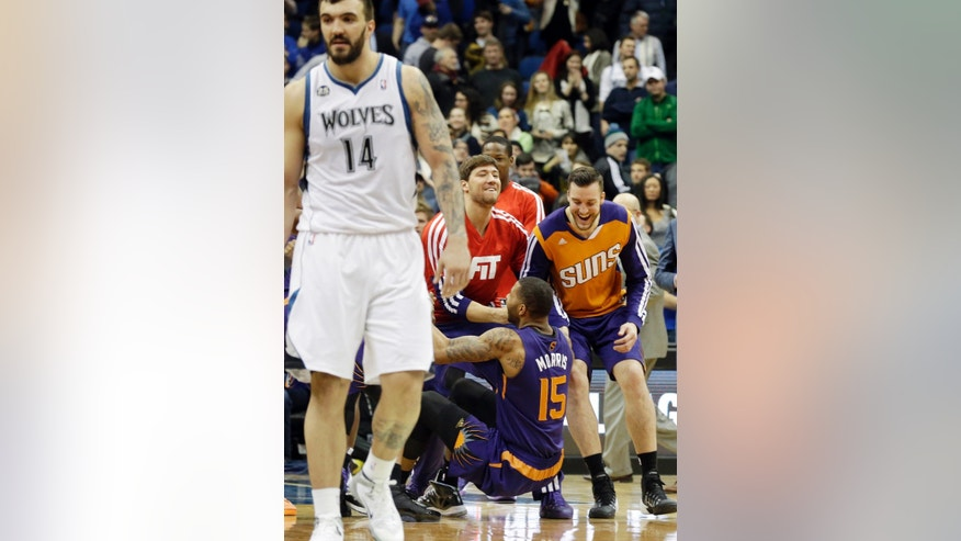 Minnesota Timberwolves' Nikola Pekovic, left, of Montenegro, leaves the court as Phoenix Suns players, including Marcus Morris (15) celebrate their come-from-behind 104-103 win in an NBA basketball game  Wednesday, Jan. 8, 2014, in Minneapolis. (AP Photo/Jim Mone)