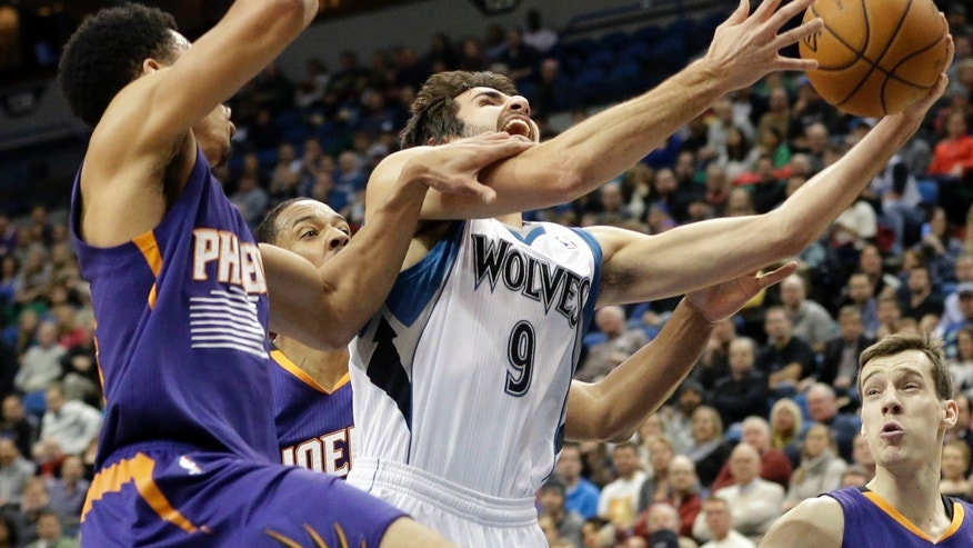 Minnesota Timberwolves' Ricky Rubio (9), of Spain, attempts a layup as Phoenix Suns' Gerald Green grabs his arm in the first quarter of an NBA basketball game on Wednesday, Jan. 8, 2014, in Minneapolis. (AP Photo/Jim Mone)