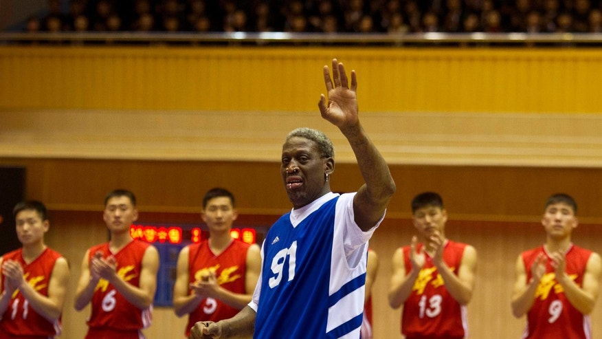 Dennis Rodman waves to North Korean leader Kim Jong Un, seated above in the stands, after singing Happy Birthday to Kim before an exhibition basketball game with U.S. and North Korean players at an indoor stadium in Pyongyang, North Korea on Wednesday, Jan. 8, 2014. (AP Photo/Kim Kwang Hyon)