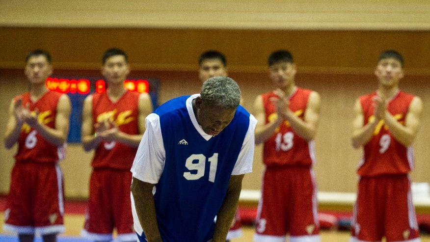 Dennis Rodman bows to North Korean leader Kim Jong Un, seated above in the stands, after singing Happy Birthday to Kim before an exhibition basketball game with U.S. and North Korean players at an indoor stadium in Pyongyang, North Korea on Wednesday, Jan. 8, 2014. (AP Photo/Kim Kwang Hyon)