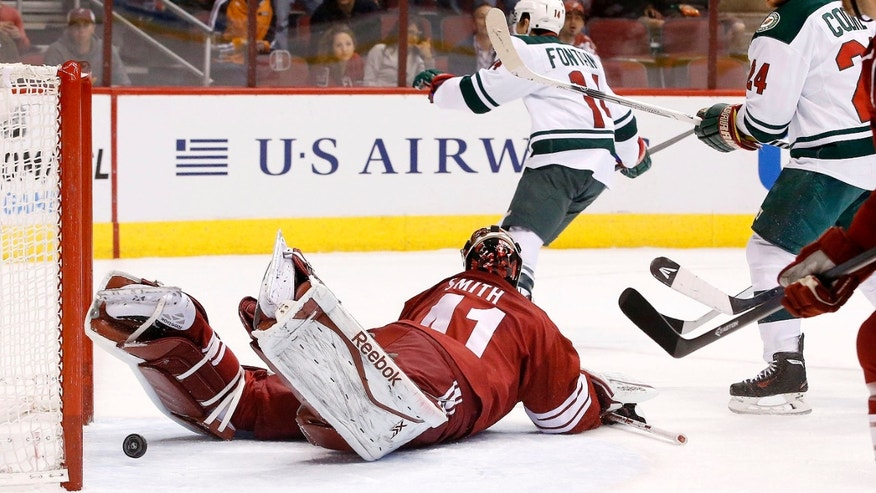 Minnesota Wild's Justin Fontaine (14) scores against Phoenix Coyotes' Mike Smith, left, as Wild's Matt Cooke (24) looks on during the first period in an NHL hockey game, Thursday, Jan. 9, 2014, in Glendale, Ariz. (AP Photo/Ross D. Franklin)