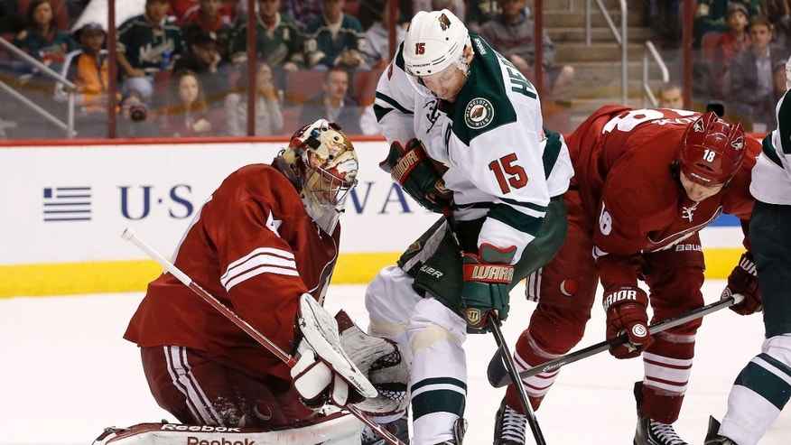 Phoenix Coyotes' Mike Smith, left, makes a save on a shot by Minnesota Wild's Dany Heatley, of Germany, as Coyotes' David Moss (18) defends during the first period in an NHL hockey game Thursday, Jan. 9, 2014, in Glendale, Ariz. (AP Photo/Ross D. Franklin)