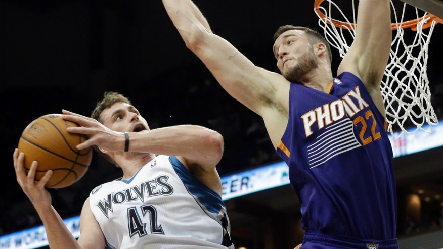 Minnesota Timberwolves' Kevin Love eyes a possible shot as Phoenix Suns' Miles Plumlee defends in the first quarter of an NBA basketball game on Wednesday, Jan. 8, 2014, in Minneapolis. (AP Photo/Jim Mone)