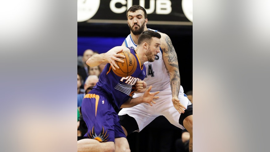 Minnesota Timberwolves' Nikola Pekovic, right, of Montenegro, attempts to slow down Phoenix Suns' Miles Plumlee in the first quarter of an NBA basketball game on Wednesday, Jan. 8, 2014, in Minneapolis. (AP Photo/Jim Mone)