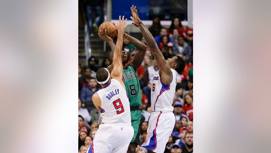 Boston Celtics forward Jeff Green, middle tries to get a shot off between Los Angeles Clippers forward Jared Dudley, left, and center DeAndre Jordan during the first half of an NBA basketball game in Los Angeles, Wednesday, Jan. 8, 2014. (AP Photo/Chris Carlson)