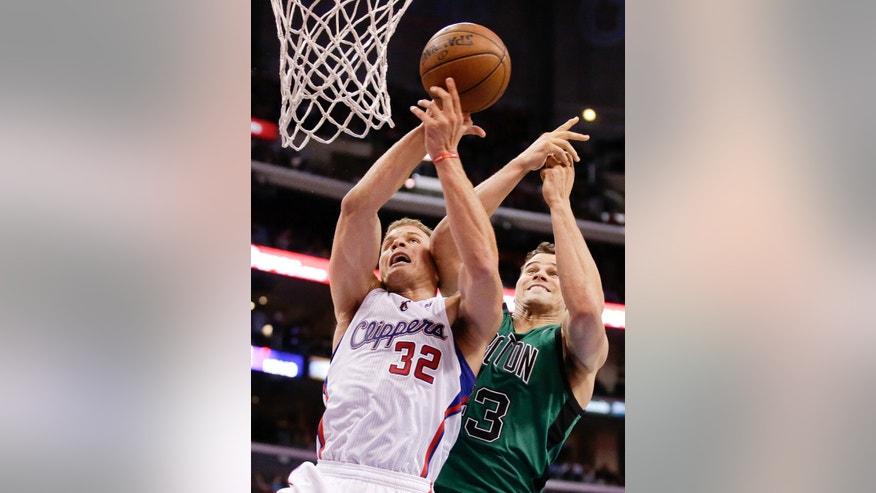 Los Angeles Clippers forward Blake Griffin, left, is fouled by Boston Celtics forward Kris Humphries during the first half of an NBA basketball game in Los Angeles, Wednesday, Jan. 8, 2014. (AP Photo/Chris Carlson)